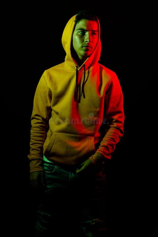 Portrait d'ado frais avec le hoodie jaune dans la lumière verte et rouge photos libres de droits