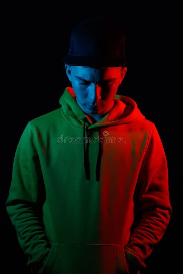 Portrait d'ado frais regardant vers le bas avec le hoodie jaune dans le bleu images stock