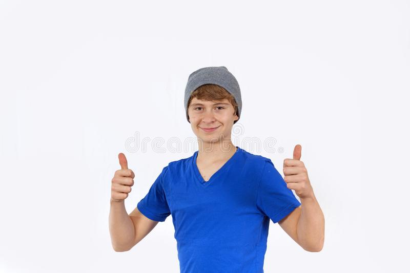 Portrait d'adolescent avec le chapeau montrant des pouces vers le haut de signe images stock