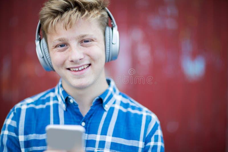 Portrait d'adolescent portant les écouteurs sans fil et le Listenin photos stock