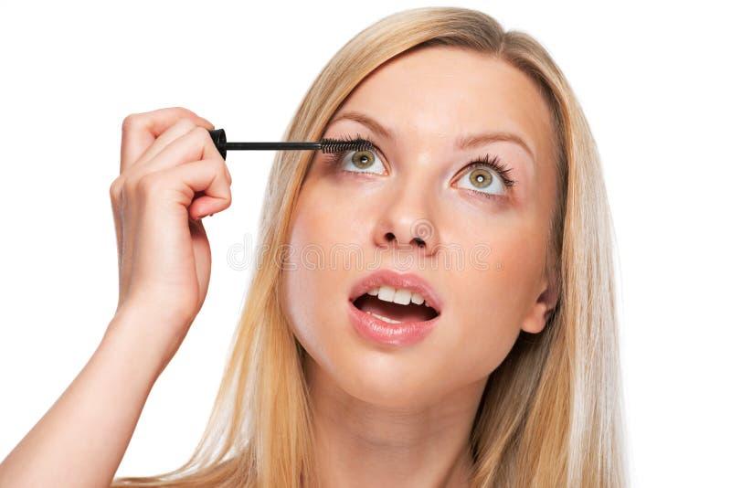 Portrait d'adolescente appliquant le mascara image stock