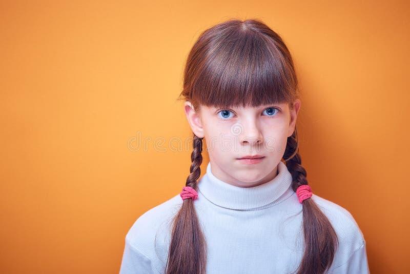 Portrait d'adolescente caucasienne avec deux tresses sur le fond coloré photos stock