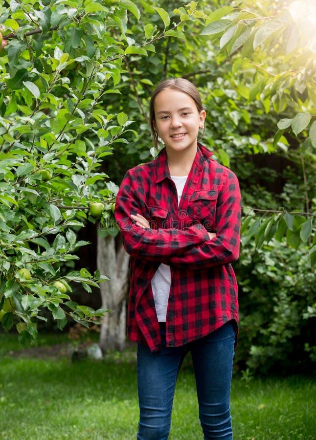 Portrait d'adolescente de sourire dans la chemise à carreaux rouge posant à l'oprchard photos libres de droits