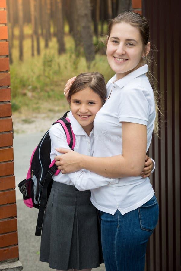Portrait d'adolescente mignonne dans l'uniforme scolaire étreignant sa mère image stock