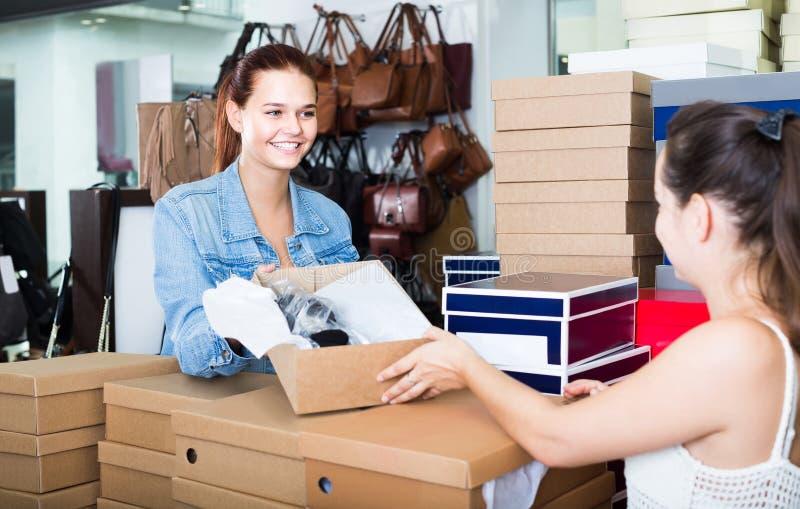 Portrait d'adolescente parlant au vendeur parmi des boîtes avec nouveau photos stock