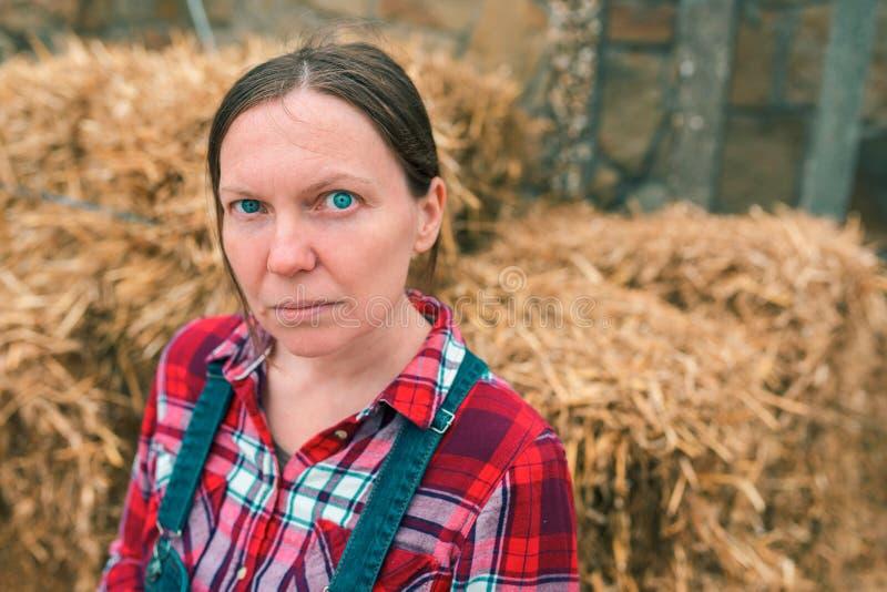 Portrait d'agriculteur féminin sérieux devant la meule de foin photo stock