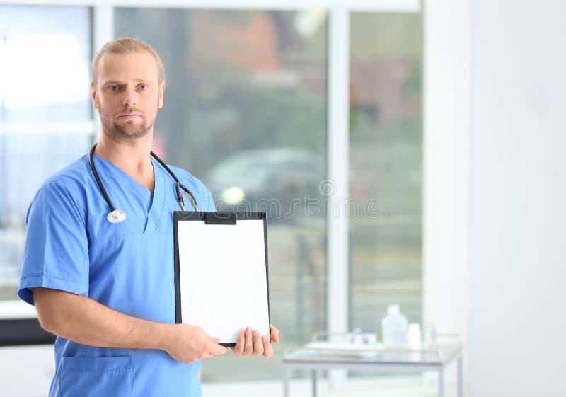 Portrait d'aide médical avec le stéthoscope et le presse-papiers dans l'hôpital photo libre de droits