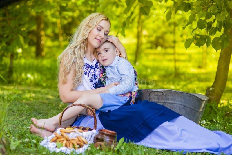 Portrait d'aimer la mère caucasienne avec son petit enfant Pose avec le panier plein des anneaux de pain dehors photographie stock libre de droits