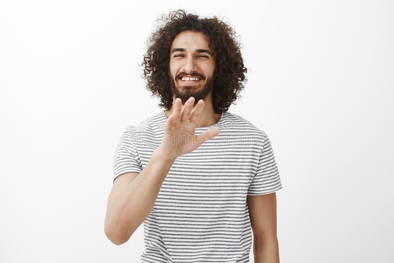 Portrait d'ami hispanique insouciant avec du charme avec les cheveux bouclés et de barbe, paume de ondulation dans aucun mercis o photo libre de droits