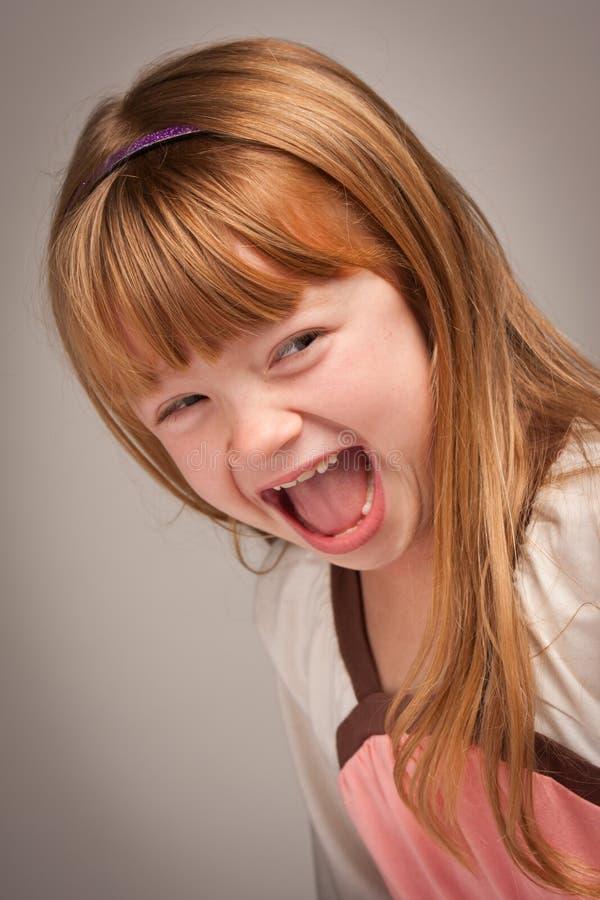 Portrait d'amusement d'une fille d'une chevelure rouge adorable sur le gris photos stock