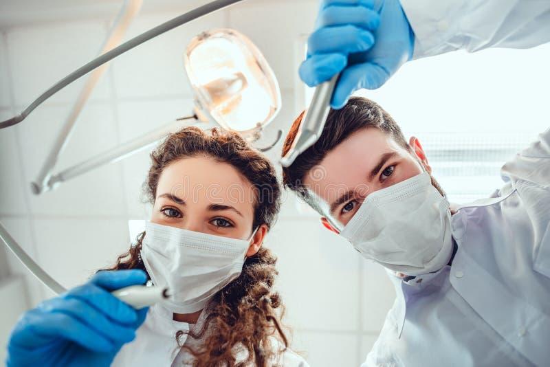 Portrait d'angle faible des dentistes masculins et f?minins portant des masques ? la clinique dentaire photographie stock