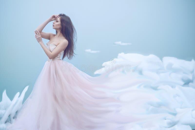 Portrait d'art d'une belle jeune nymphe dans la robe de boule sans bretelles luxueuse s'élevant dans les nuages mous image libre de droits