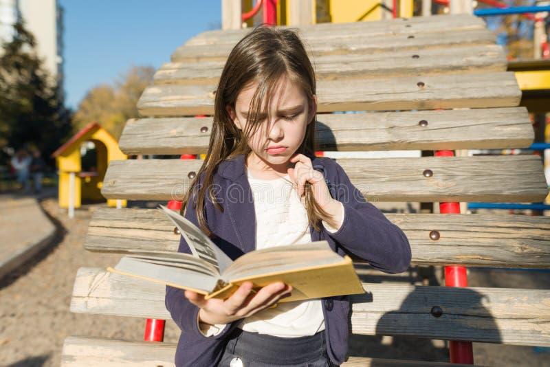 Portrait d'Autdoor de petite fille offens?e Livre de lecture d'enfant, boudant offendedly ses lèvres photos libres de droits