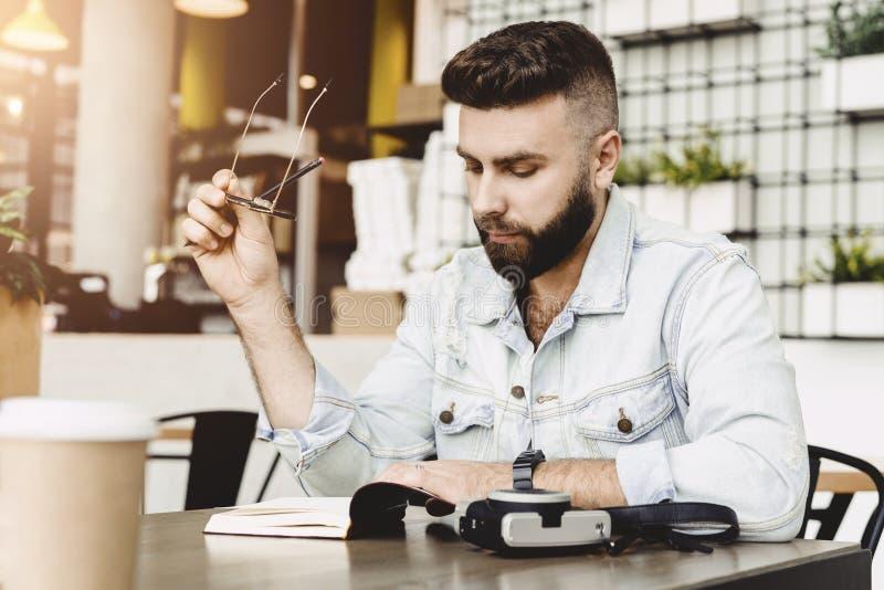 Portrait d'auteur masculin barbu Le type s'assied avec le carnet en caf? ? la table, tient le crayon dans sa main, regarde pensiv image stock