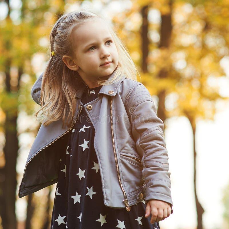 Portrait d'automne de peu de fille en parc Peu de fille ayant l'amusement en automne Enfance heureux Fille élégante jouant en par images stock