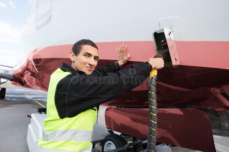 Portrait d'avion de remplissage de membre d'équipage sur la piste photographie stock libre de droits