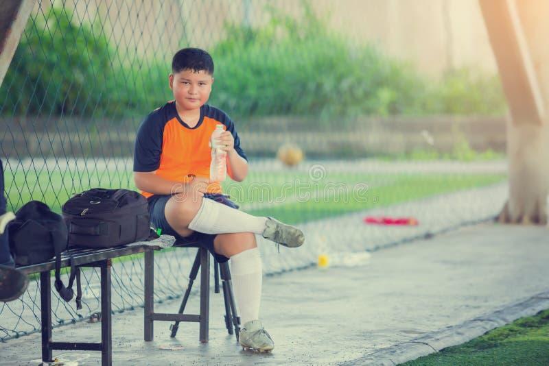 Portrait d'eau potable d'adolescent asiatique au terrain de football apr?s la formation photographie stock