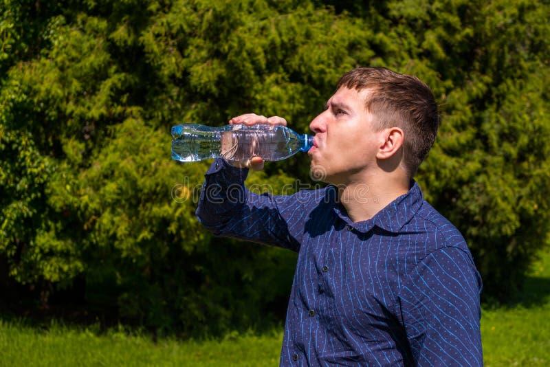Portrait d'eau potable des hommes d'une bouteille, dans la position bleue de chemise extérieure en parc photo stock