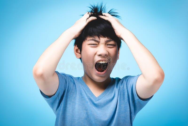 Portrait d'enfant asiatique fâché sur le fond bleu images stock