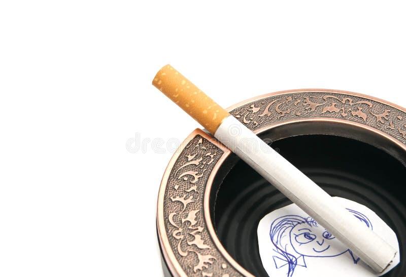 Portrait d'enfant et de cigarette dans le cendrier photos stock