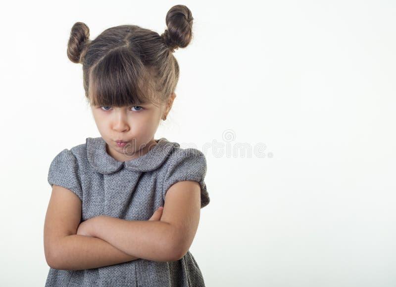 Portrait d'enfant européen mignon offensé et déprimé avec les lèvres de froncement de sourcils et pinçantes de cheveux de brune,  photo libre de droits