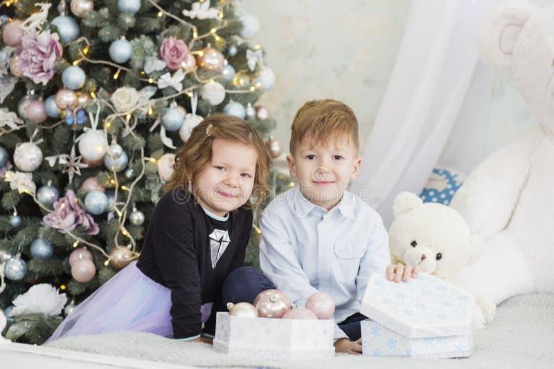 Portrait d'enfants heureux - gar?on et fille Petits enfants dans des d?corations de No?l blanc de soeur d'isolement par fr?re de  images stock
