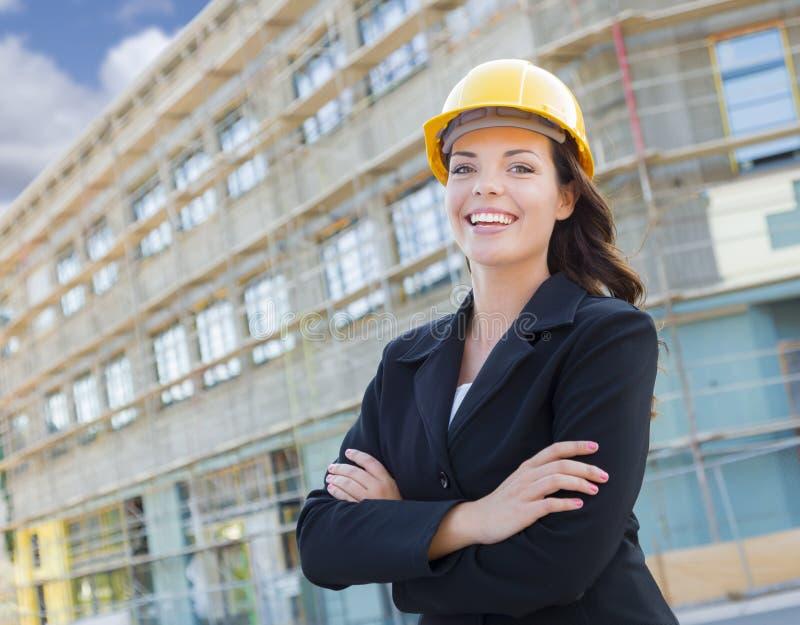 Portrait d'entrepreneur femelle utilisant le casque antichoc à la construction S photo stock