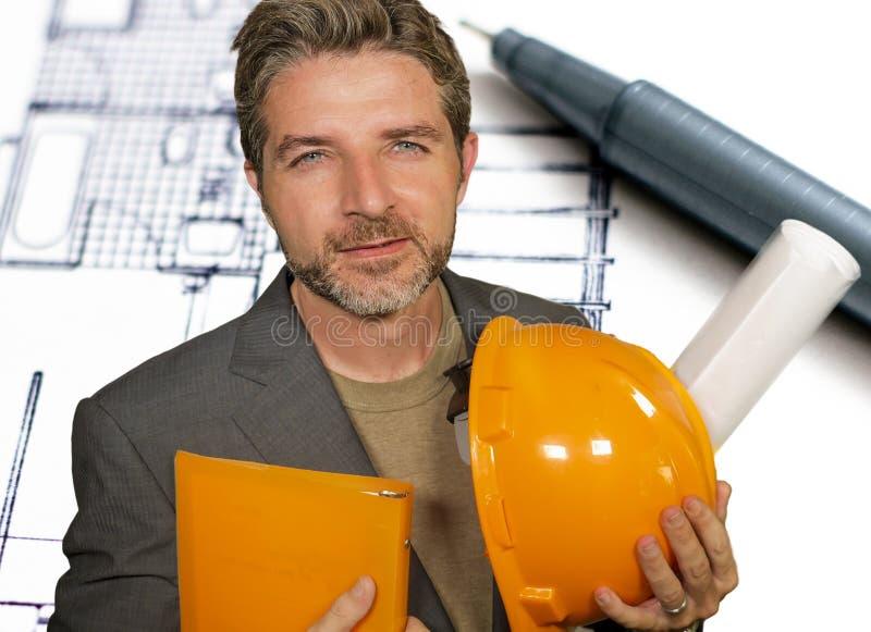 Portrait d'entreprise des modèles attrayants d'architecte d'homme de participation de casque efficace et sûr de constructeur et d photo stock