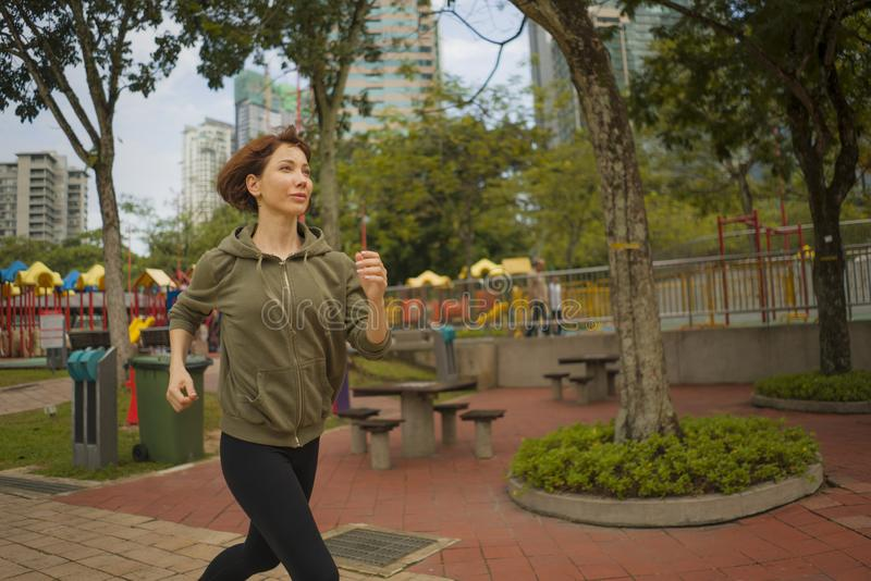 Portrait d'extérieur de jeune femme attirante et active de taqueur dans le fonctionnement supérieur et pulser de hoodie dans la s photo libre de droits