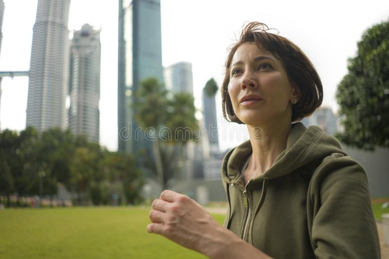 Portrait d'extérieur de jeune femme attirante et active de taqueur dans le fonctionnement supérieur et pulser de hoodie dans la s photos stock