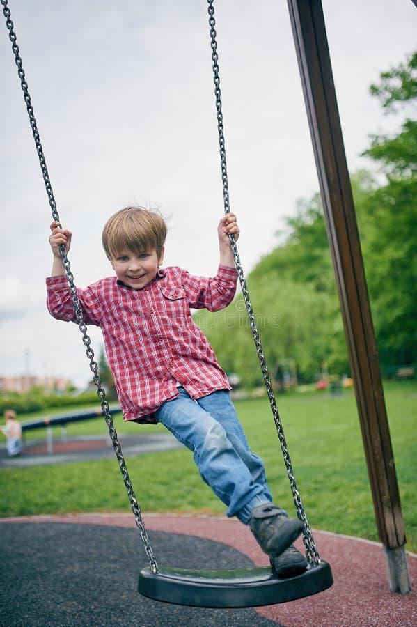 Portrait d'extérieur du garçon riant préscolaire mignon balançant sur une oscillation au terrain de jeu images stock