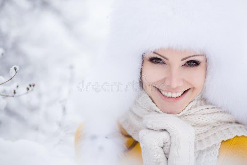 Portrait d'hiver de belle femme de sourire avec des flocons de neige en fourrures blanches photo stock