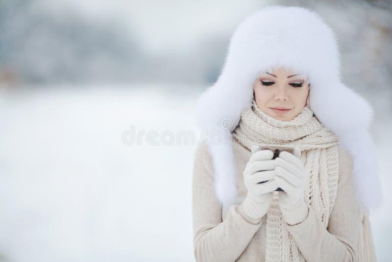 Portrait d'hiver de belle femme de sourire avec des flocons de neige en fourrures blanches photographie stock libre de droits
