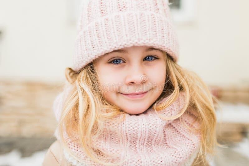 Portrait d'hiver de fille d'enfant de sourire dans le chapeau et l'écharpe photographie stock