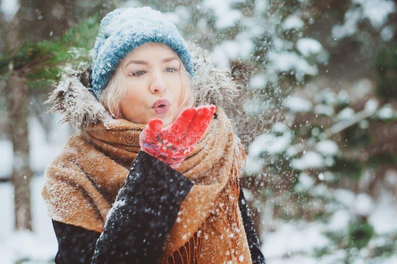 Portrait d'hiver de jeune femme heureuse marchant dans la forêt neigeuse dans l'équipement chaud image libre de droits