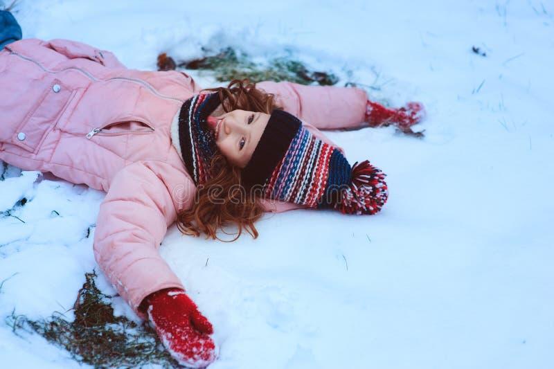 portrait d'hiver de jouer heureux de fille d'enfant extérieur dans le jardin neigeux, faisant l'ange de neige photos stock