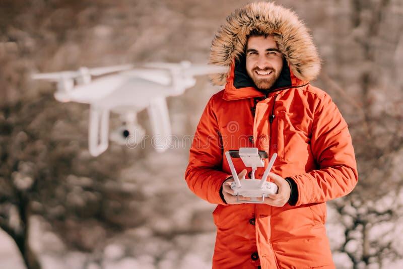 Portrait d'hiver de l'homme portant le bourdon chaud de vol de veste, quadcopter blanc de pilotage images stock