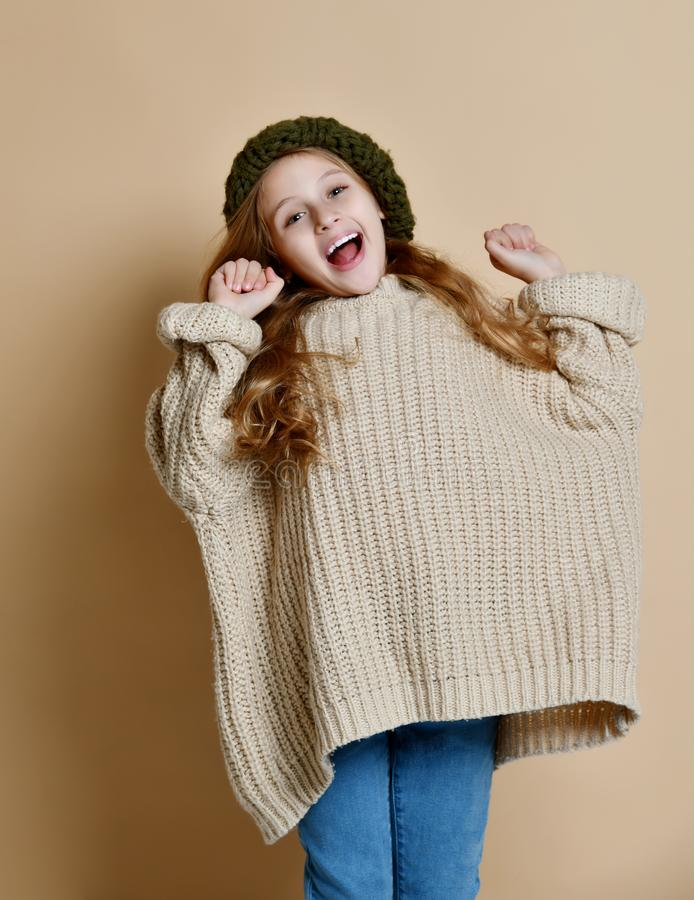 Portrait d'hiver de la petite fille heureuse utilisant le chapeau et le chandail tricot?s photo stock