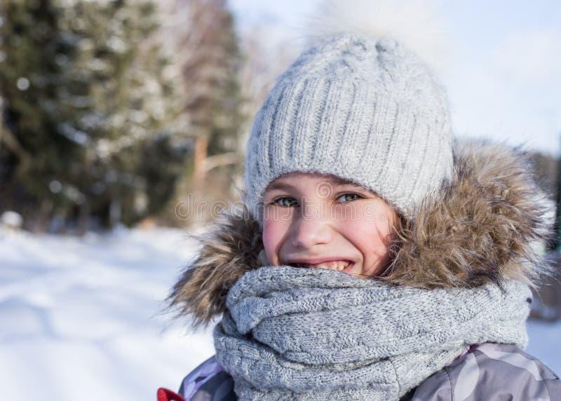 Portrait d'hiver de la petite fille heureuse utilisant le chapeau et l'écharpe tricotés photos stock