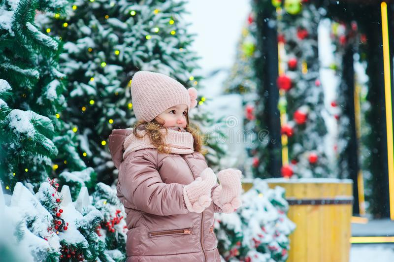 Portrait d'hiver et de Noël de la marche heureuse de bébé extérieure dans le jour neigeux, ville décorée pendant des vacances photos libres de droits