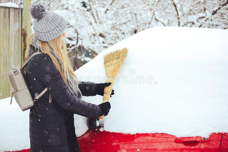 Portrait d'hiver d'une neige de nettoyage de jeune femme d'une voiture La beauté Girl modèle blond rit et nettoie gaiement la nei photo libre de droits