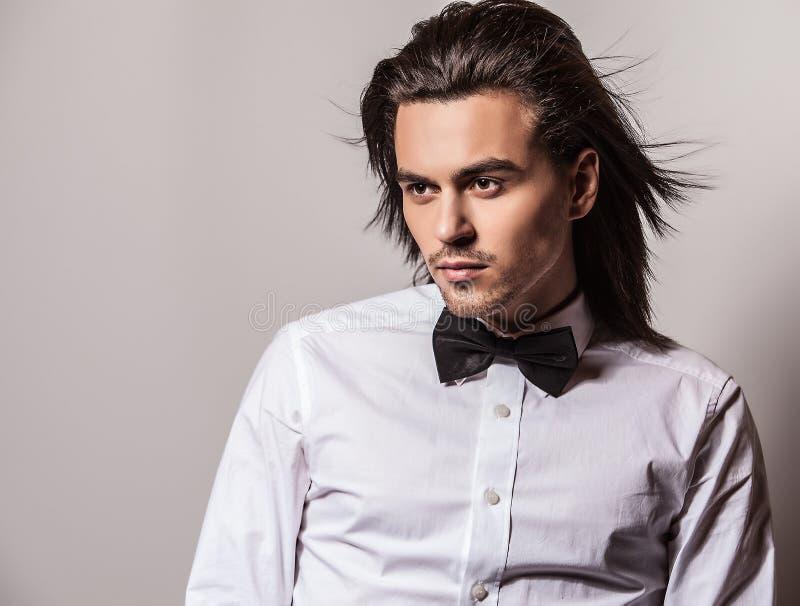 Portrait d'homme élégant aux cheveux longs bel avec le lien d'arc. photo libre de droits