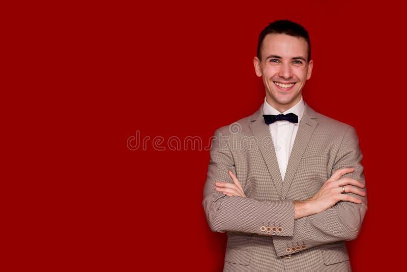 Portrait d'homme élégant bel de sourire dans le costume blanc élégant sur le fond rouge Type d'affaires photographie stock