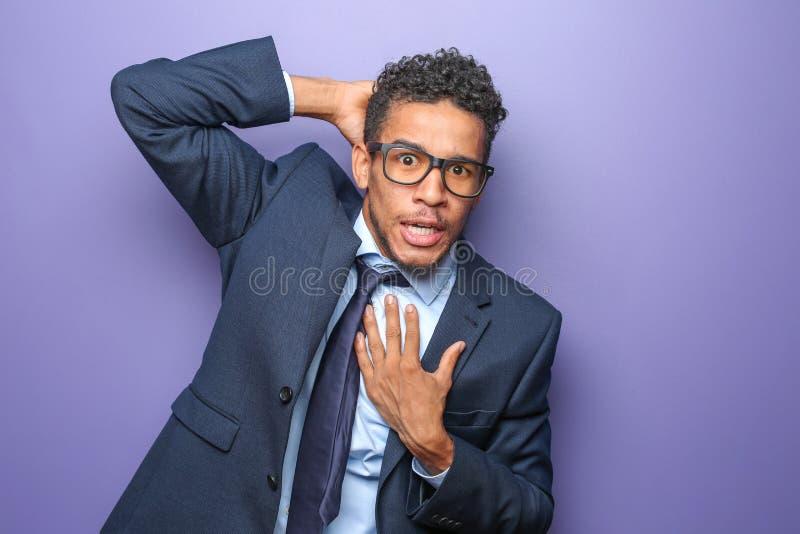 Portrait d'homme d'affaires afro-américain effrayé sur le fond de couleur image stock