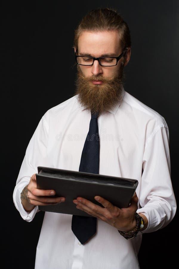 Portrait d'homme d'affaires barbu de hippie sérieux avec des documents Patron en verres posant dans le costume photos stock