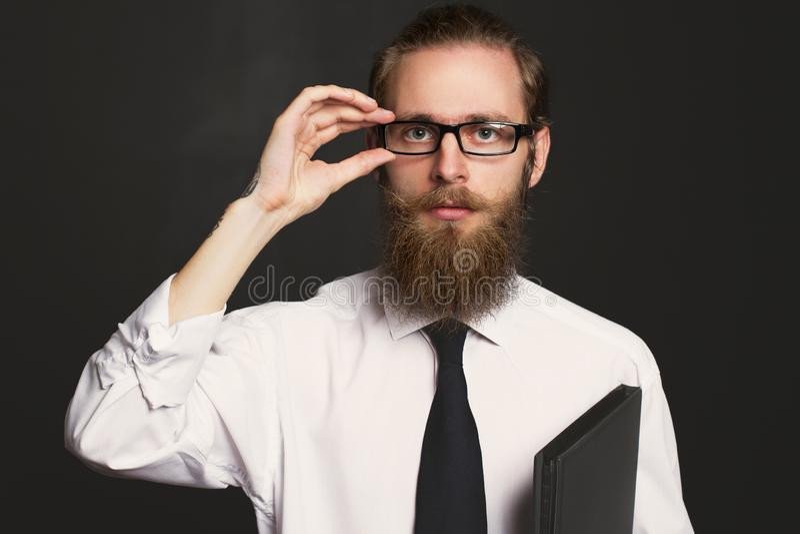 Portrait d'homme d'affaires barbu de hippie sérieux avec des documents Patron en verres posant dans les affaires image stock