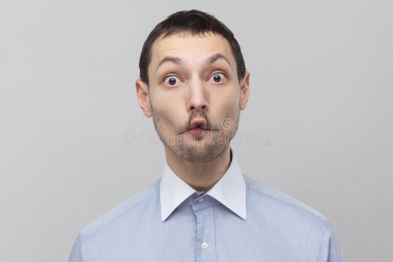 Portrait d'homme d'affaires bel drôle de poil dans la position bleue classique de chemise regardant la caméra avec le visage éton photographie stock libre de droits