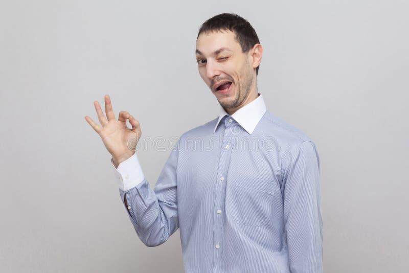 Portrait d'homme d'affaires bel fol drôle de poil la position bleu-clair classique de chemise avec le signe correct et en regarda photos stock