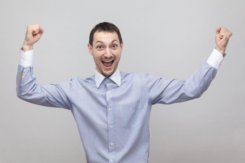 Portrait d'homme d'affaires bel joyeux enthousiaste de poil dans la position bleu-clair classique de chemise avec les bras augmen image stock