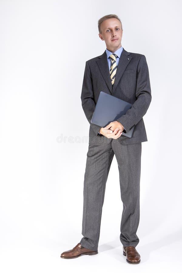 Portrait d'homme d'affaires caucasien tranquille avec l'ordinateur portable contre le blanc image libre de droits